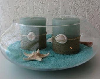 Set of two candles decorated with shells and sand in the vase
