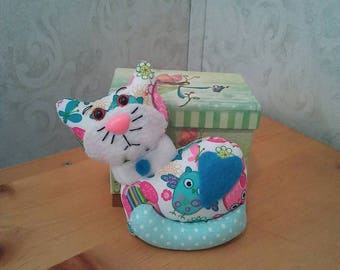 Cat in multicolored cotton novelty print. Safety eyes n nose. Hypoallergenic stuffing. Turquoise felt heart. Velcro collar. Measures 5 high.