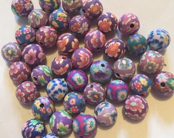 Pack of 40 x 10mm polymer clay round mix of purple themed flower etc beads.