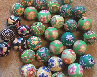 Pack of 33 x 12mm polymer clay round mix of green themed flower etc beads.