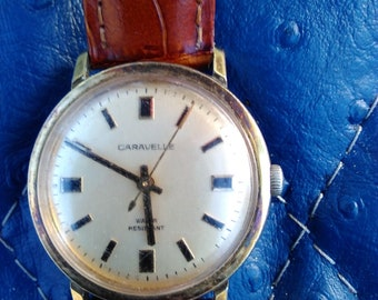 Vintage Caravelle By Bulova Mens Mechanical windup Wrist Watch with genuine leather wrist strap keeps great time.