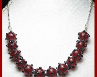Handmade, lamp-work glass beads on fine silver plated chain.  Deep cherry red with raised black dots.  Made by Teluma Designs. One Only.