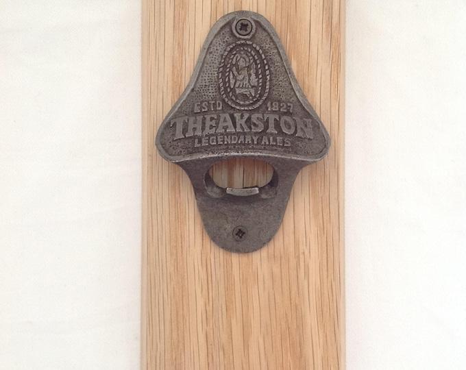 Wall mounted  cast iron Theakstons Bottle opener on Oak Plaque