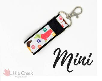 Dachshund wearing sweaters mini key fob, wiener dogs small keychain, paw prints on white with black