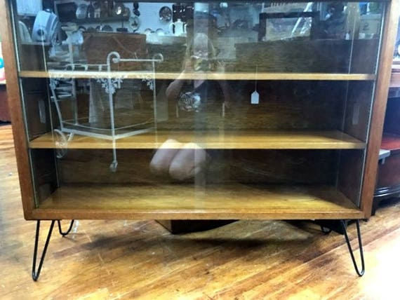 Mid century bookcase with sliding glass doors and hairpin legs