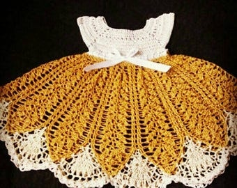 Crocheted baby dress in gold and cream.