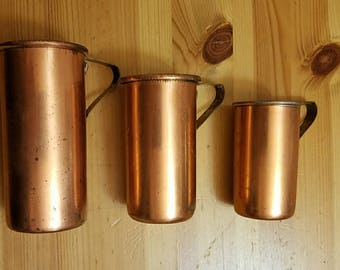 Set of three vintage copper plated measuring cups.