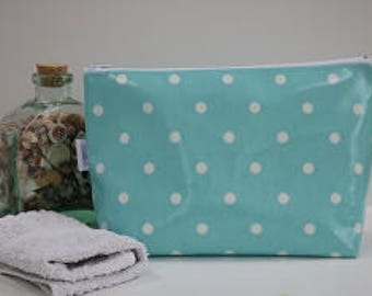 Stand alone oilcloth washbag in turquoise and white spot design.