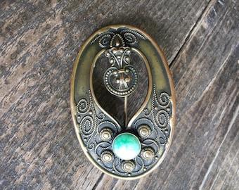 Antique Art Nouveau Sash Pin.  Cira 1890's =  Pre W.W.1 . Brass metal . Green Glass Cabochon. Period pin closure .