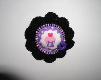brooch is crochet and fabric printed black and purple cupcake