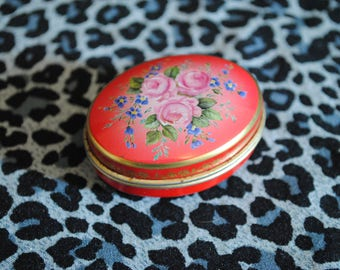 Vintage oval tin featuring rose design