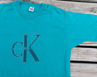 90's Calvin Klein distressed teal blue green t-shirt Made in USA by Fruit of the Loom large