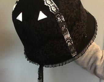 Black cloche hat with white details.