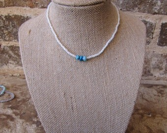 white beaded choker with three blue natural beads