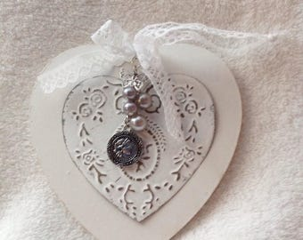 Placed on a wooden heart hammered metal heart