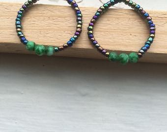 Green and black circular earrings