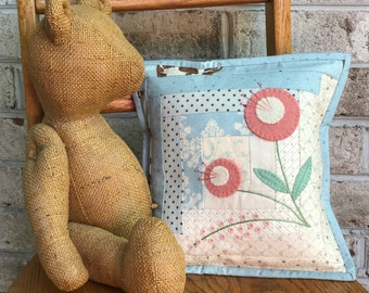 Beautiful log cabin pillow with wool flowers