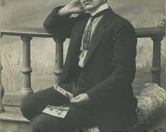 Sad man looking at photographs antique photo