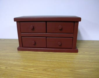 Four drawer apothecary table or counter cabinet. Solid cranberry red in color.