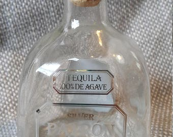 Empty glass Patron tequila bottle with labels