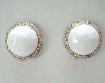"""Milk glass clip on earrings. Vintage earrings signed Bergere about 1"""" diameter. Center of milk glass. Surrounded with rhinestones."""
