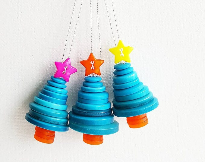 Three brilliant blue button Christmas trees