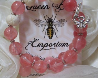 Pink and cream colored glass beads with silver toned accents and a dangling bee charm memory wire bracelet
