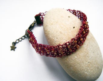 Metal bracelet crocheted red and iridescent glass beads.