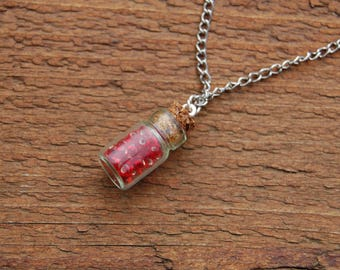Pendant jar with seed beads, red glass with sterling silver material.