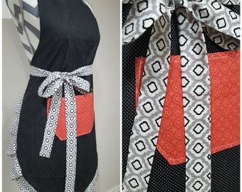 Adult apron. Woman's apron. Black with tiny polka dots on main. Coral diamond shapes on pocket. Black/white/gray shapes on ties & frills.