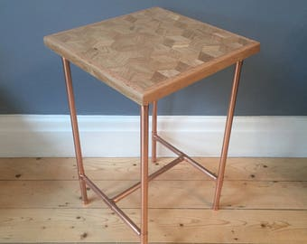 Side table in a retro industrial style with a copper pipe frame and reclaimed oak geometric cube design top
