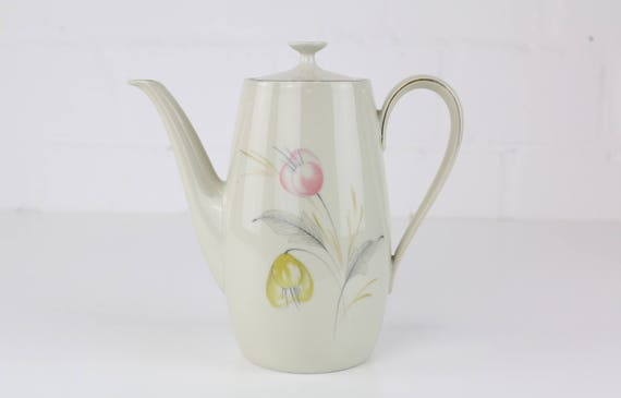 Small vintage teapot with delicate floral motif in pastel-colored antique coffee pot