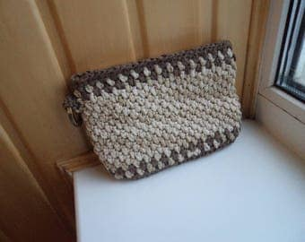 Crocheted delicate light brown bag on hand