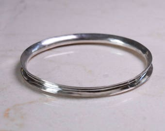 Handraised silver anticlastic wave bangle