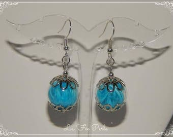 Dangle earrings in turquoise blue glass topped with feathers