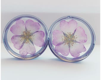 Pink and white flower plugs, ear guages, ear stretchers, ear plugs.