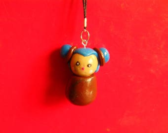 cute little kokeshi is hanging on a cell phone or bag in hand