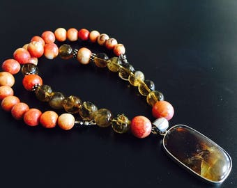 A wood coral and crystal beaded necklace with amber pendant