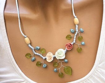 Necklace three flowers and green leaves