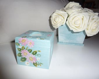 box square featuring a pink flower on blue background