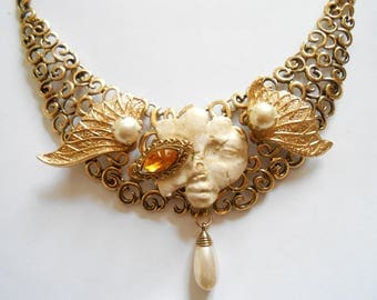 Necklace plastron half angel and demon gold.
