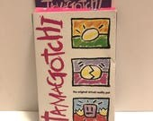 Vintage purple TAMAGOTCHI by Bandai 1996 - 97, in box with battery strip intact