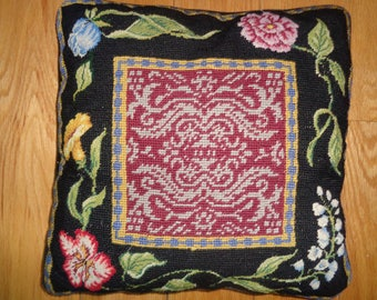 Vintage Needlepoint Pillow with hand sewn petit needlepoint flowers against a black background and a black velvet zippered back opening