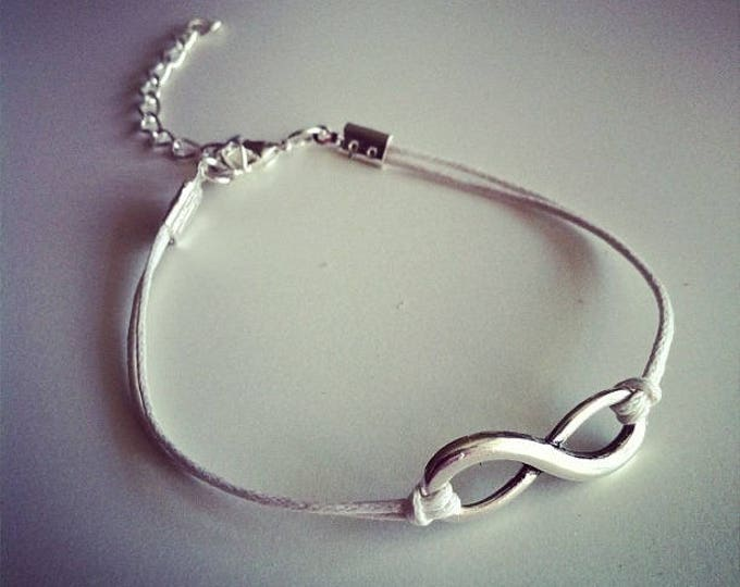 White cord with silver infinity sign bracelet