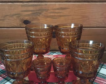 Vintage Indiana glass in amber-4 goblets and 2 matching cordial glasses/shot glasses with thumbprint design and square bottom.