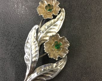 Silver flower spray brooch with green stones
