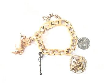 Monet Gilt Charm Bracelet with Four Charms-Bull,Baton, Cherubs, & Prayer