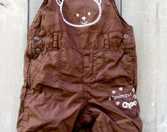 Overall layering piece for newborn . Adjustable straps and snap leg open. Artwork design animaux.
