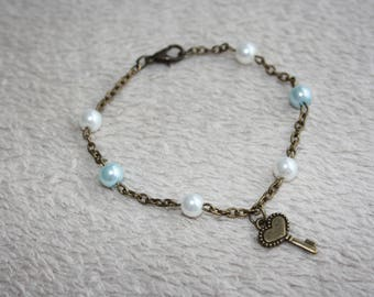Bronze chain bracelet blue and white beads and key pendant