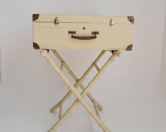 Old suitcase bedside on tripod style patinated napoleon linen